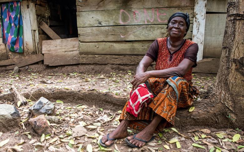 Tahtadan yapılmış evinin önünde oturan yaşlı bir kadın