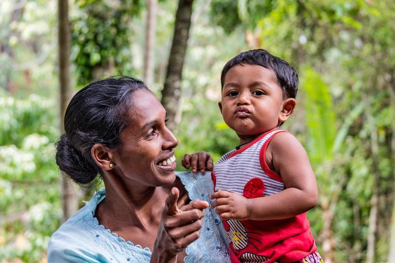 Kendilerini görüntüleyen kameraya poz vermeye çalışan bir kadın ve çocuğu